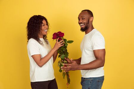 Flowers for smile. Valentines day celebration, happy african-american couple isolated on yellow studio background. Concept of human emotions, facial expression, love, relations, romantic holidays.