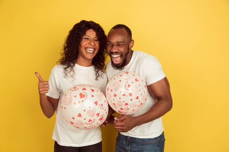 Holding balloons. Valentines day celebration, happy african-american couple isolated on yellow studio background. Concept of human emotions, facial expression, love, relations, romantic holidays.