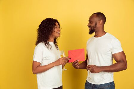 Giving red envelope. Valentines day celebration, happy african-american couple isolated on yellow studio background. Concept of human emotions, facial expression, love, relations, romantic holidays. Stok Fotoğraf