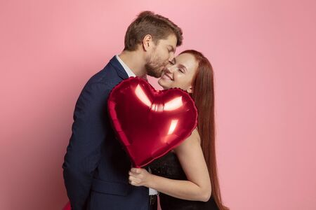 Happy holding balloons shaped hearts. Valentines day celebration, happy caucasian couple on coral background. Concept of human emotions, facial expression, love, relations, romantic holidays.