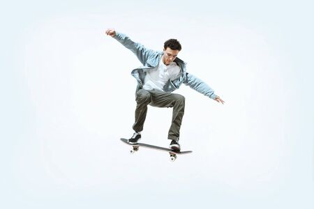 Caucasian young skateboarder riding isolated on a white studio background. Man in casual clothing training, jumping, practicing in motion. Concept of hobby, healthy lifestyle, youth, action, movement.