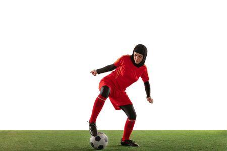 Giocatore di calcio o di calcio femminile arabo isolato su sfondo bianco per studio. Giovane donna che calcia la palla, si allena, si esercita in movimento e azione. Concetto di sport, hobby, stile di vita sano. Archivio Fotografico