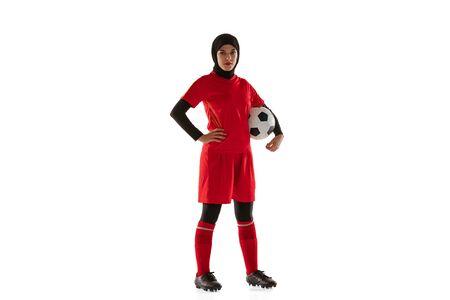 Arabische vrouwelijke voetbal of voetbalster die op witte studioachtergrond wordt geïsoleerd. Jonge vrouw die de bal vasthoudt, traint, oefent in beweging en actie. Concept van sport, hobby, gezonde levensstijl.