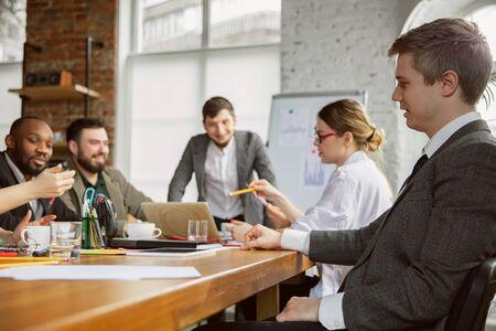 Eine Familie. Gruppe junger Geschäftsleute, die ein Treffen haben. Diverse Gruppe von Mitarbeitern diskutieren neue Entscheidungen, Pläne, Ergebnisse, Strategie. Kreativität, Arbeitsplatz, Geschäft, Finanzen, Teamwork.