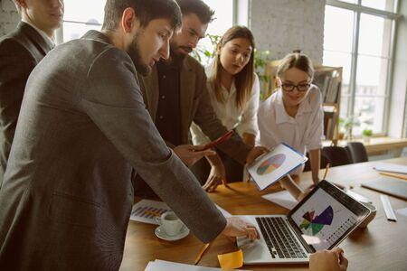 Budowanie zespołu. Grupa młodych profesjonalistów o spotkaniu. Zróżnicowana grupa współpracowników omawia nowe decyzje, plany, wyniki, strategię. Kreatywność, miejsce pracy, biznes, finanse, praca zespołowa.