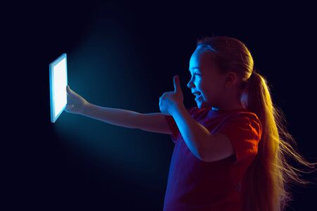 Shows thumbs up. Caucasian girls portrait on dark background in neon light. Beautiful female model using tablet. Concept of human emotions, facial expression, sales, ad, modern tech, gadgets.