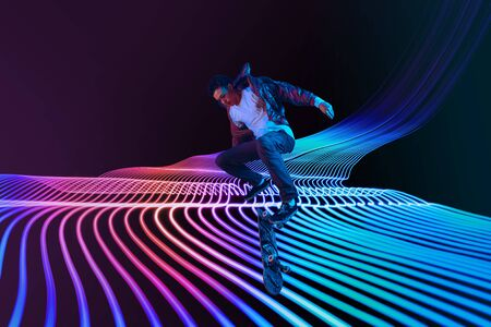 Caucasian young skateboarder riding on dark neon lighted line background. Training in action and motion on colorful waves. Concept of hobby, healthy lifestyle, youth, action, movement, modern style.