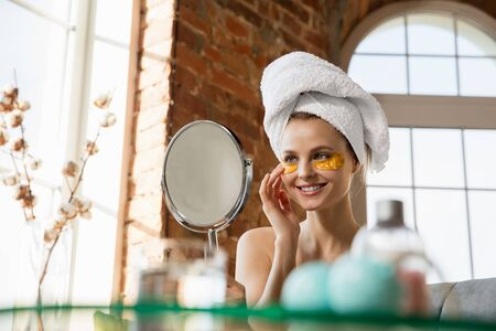 Beauty Day. Woman wearing towel doing her daily skincare routine at home. Putting on golden under eye patches, looking on her reflection in mirror. Concept of beauty, self-care, cosmetics, youth.