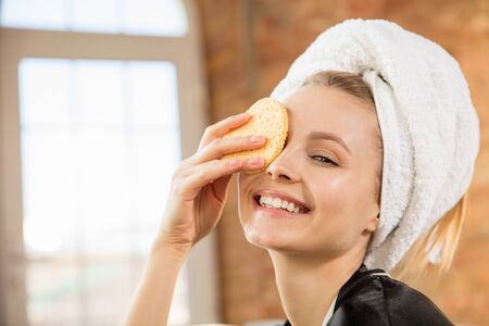 Beauty Day. Close up of woman wearing silk robe doing her daily skincare routine at home. Looks satisfied, putting on moisturizer on her face skin, smiling. Concept of beauty, self-care, cosmetics.
