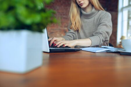 Beautiful caucasian business lady working in office with laptop. Young female model in co-working place makes notes, drinks coffee, performes tasks. Concept of business, finance, freelance, open space. Stock Photo