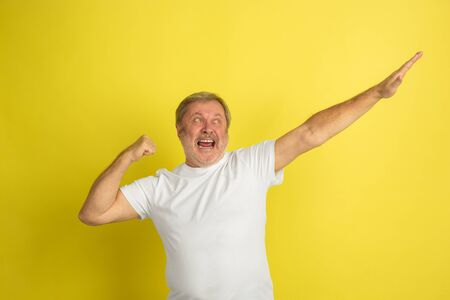 Successful winners gesture. Caucasian man portrait isolated on yellow studio background. Beautiful male model in white shirt posing. Concept of human emotions, facial expression, sales, ad. Copyspace. Zdjęcie Seryjne