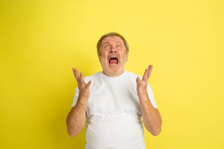 Astonished, shocked, wondered screams. Caucasian man portrait isolated on yellow studio background. Beautiful male model in white shirt posing. Concept of human emotions, facial expression, sales, ad.