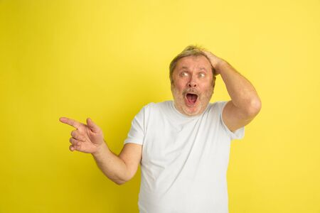 Astonished, shocked, pointing at side. Caucasian man portrait isolated on yellow studio background. Beautiful male model in white shirt posing. Concept of human emotions, facial expression, sales, ad.