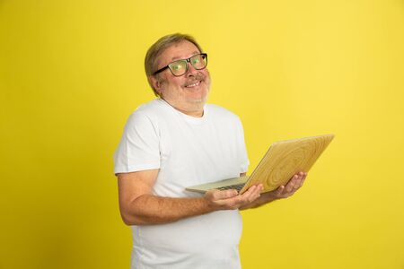 Using laptop, smiling. Caucasian man portrait isolated on yellow studio background. Beautiful male model in white shirt posing. Concept of human emotions, facial expression, sales, ad. Copyspace.