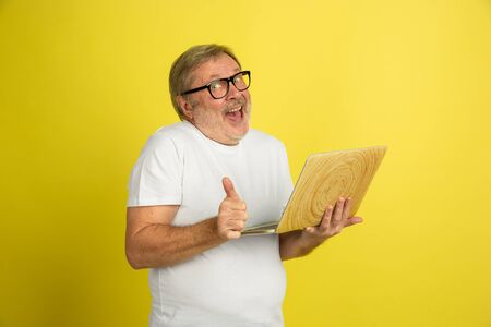 Using laptop, thumb up. Caucasian man portrait isolated on yellow studio background. Beautiful male model in white shirt posing. Concept of human emotions, facial expression, sales, ad. Copyspace.