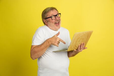 Using laptop, pointing on. Caucasian man portrait isolated on yellow studio background. Beautiful male model in white shirt posing. Concept of human emotions, facial expression, sales, ad. Copyspace.