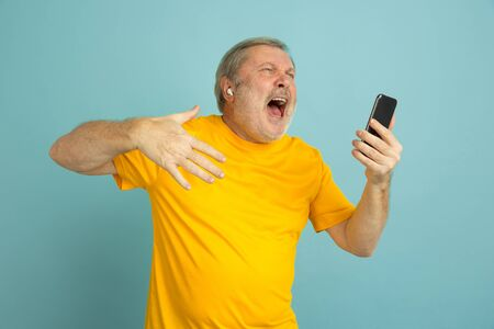 Using smartphone, screaming like winner. Caucasian man portrait on blue studio background. Beautiful male model in yellow shirt. Concept of human emotions, facial expression, sales, ad, bet. Copyspace.