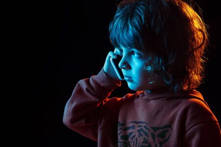 Cute talking on phone. Close up. Caucasian boys portrait on dark studio background in neon light. Beautiful curly model. Concept of human emotions, facial expression, sales, ad, modern tech, gadgets.