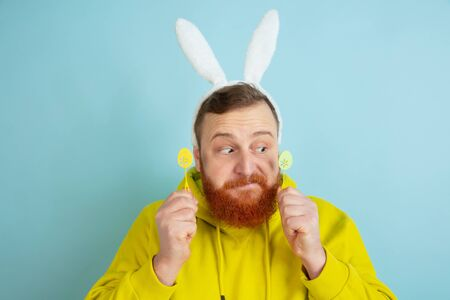 Caucasian man with traditional decor as an Easter bunny with bright casual clothes on blue studio background. Happy easter greetings. Concept of human emotions, facial expression, holidays. Copyspace.