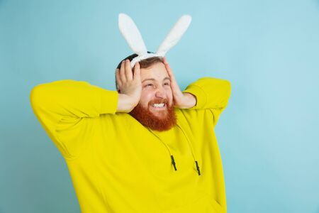 Shocked, astonished. Caucasian man as an Easter bunny with bright casual clothes on blue studio background. Happy easter greetings. Concept of human emotions, facial expression, holidays. Copyspace. Stockfoto