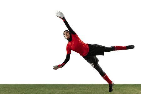 Jugador de fútbol o fútbol femenino árabe, portero sobre fondo blanco de estudio. Mujer joven atrapando pelota, entrenando, protegiendo goles en movimiento y acción. Concepto de deporte, afición, estilo de vida saludable. Foto de archivo