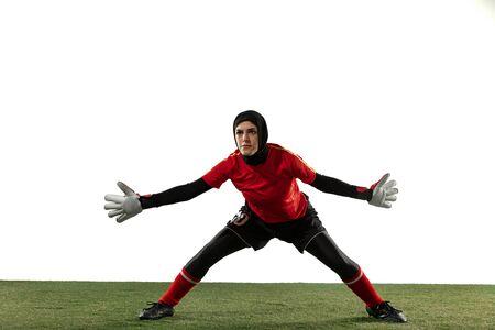 Arabischer weiblicher Fußball- oder Fußballspieler, Torhüter auf weißem Studiohintergrund. Junge Frau, die Ball fängt, trainiert, Ziele in Bewegung und Aktion schützt. Konzept des Sports, des Hobbys, des gesunden Lebensstils.