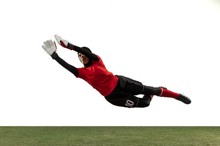 Arabian female soccer or football player, goalkeeper on white studio background. Young woman catching ball, training, protecting goals in motion and action. Concept of sport, hobby, healthy lifestyle.