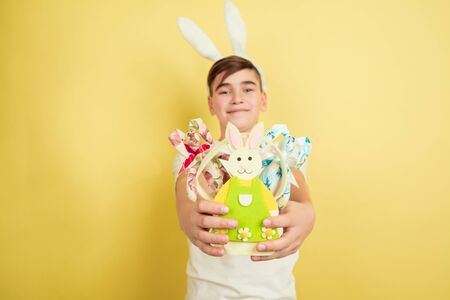 Toys giving. Decorating. Caucasian boy as an Easter bunny on yellow studio background. Happy easter greetings. Beautiful male model. Concept of human emotions, facial expression, holidays. Copyspace.