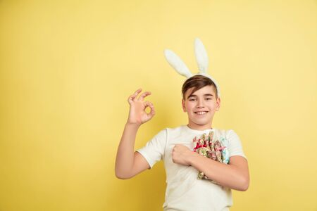 Showing nice. Decorating. Caucasian boy as an Easter bunny on yellow studio background. Happy easter greetings. Beautiful male model. Concept of human emotions, facial expression, holidays. Copyspace.