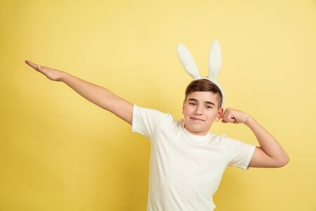 Successful winner gesture. Caucasian boy as an Easter bunny on yellow studio background. Happy easter greetings. Beautiful male model. Concept of human emotions, facial expression, holidays. Copyspace.