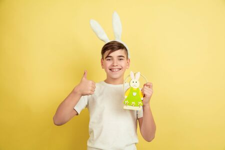 Thumb up. Decorating. Caucasian boy as an Easter bunny on yellow studio background. Happy easter greetings. Beautiful male model. Concept of human emotions, facial expression, holidays. Copyspace.