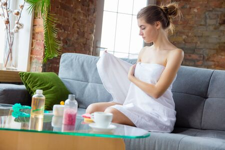 Beauty Day for yourself. Long haired woman wearing towel doing her daily skincare routine at home. Sits on sofa, preparing for putting moisturizer, massaging. Concept of beauty, self-care, cosmetics.