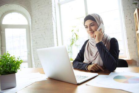 Telefonieren, aufgepasst. Schöne arabische Geschäftsfrau, die Hijab trägt, während sie im Openspace oder im Büro arbeitet. Berufskonzept, Freiheit im Geschäftsbereich, Führung, Erfolg, moderne Lösung. Standard-Bild