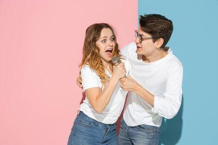 Wspólne śpiewanie piosenki. Młody i szczęśliwy mężczyzna i kobieta w ubranie na różowym, niebieskim tle dwukolorowym. Pojęcie ludzkich emocji, mimiki, relacji, reklamy. Piękna para kaukaski.