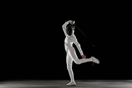 Graceful. Teen girl in fencing costume with sword in hand isolated on black background. Young female model practicing and training in motion, action. Copyspace. Sport, youth, healthy lifestyle. Banque d'images