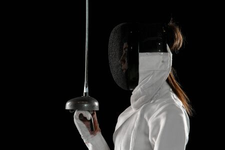 Teen girl in fencing costume with sword in hand isolated on black background. Young female model practicing and training in motion, action. Copyspace. Sport, youth, healthy lifestyle. Close up. Stockfoto