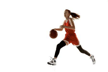 Giovane giocatore di basket femminile caucasico in azione, movimento in esecuzione isolato su priorità bassa bianca. Ragazza sportiva dai capelli rossi. Concetto di sport, movimento, energia e stile di vita dinamico e sano. Addestramento.