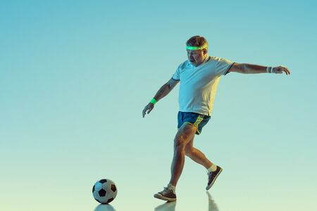 Senior man playing soccer, football on gradient background in neon light. Caucasian male model in great shape stays active, sportive. Concept of sport, activity, movement, wellbeing, healthy lifestyle.