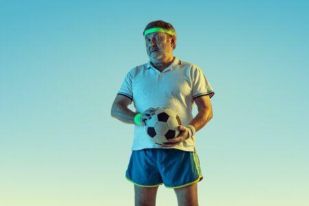 Älterer Mann, der Fußball, Fußball auf Steigungshintergrund im Neonlicht spielt. Kaukasisches männliches Model in toller Form bleibt aktiv und sportlich. Konzept von Sport, Aktivität, Bewegung, Wohlbefinden, gesunde Lebensweise.