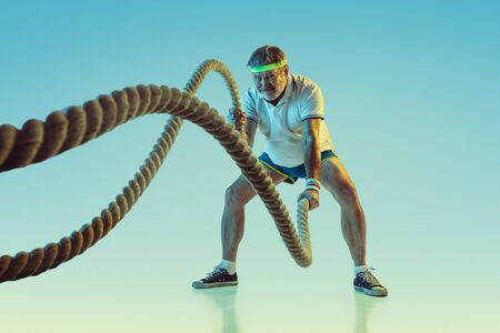 Senior man training with ropes on gradient background in neon light. Caucasian male model in great shape stays active, sportive. Concept of sport, activity, movement, wellbeing, healthy lifestyle.