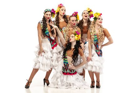 Beautiful young caucasian women in carnival and stylish masquerade costumes with flowers dancing on white studio background. Concept of holidays celebration, festive time, dance, party, having fun.