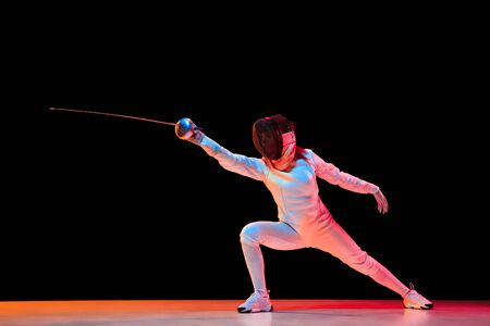 Forward. Teen girl in fencing costume with sword in hand isolated on black background, neon light. Young model practicing and training in motion, action. Copyspace. Sport, youth, healthy lifestyle. Foto de archivo