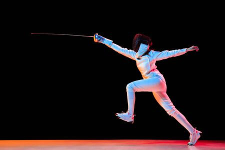 Forward. Teen girl in fencing costume with sword in hand isolated on black background, neon light. Young model practicing and training in motion, action. Copyspace. Sport, youth, healthy lifestyle. Stockfoto