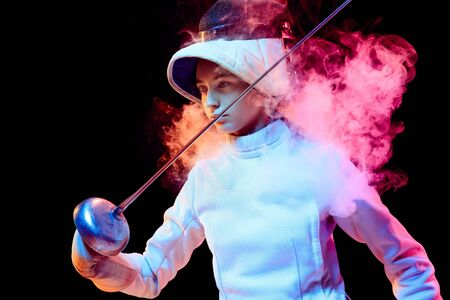 Pride. Teen girl in fencing costume with sword in hand isolated on black background, neon lighted smoke. Practicing and training in motion, action. Copyspace. Sport, youth, healthy lifestyle.