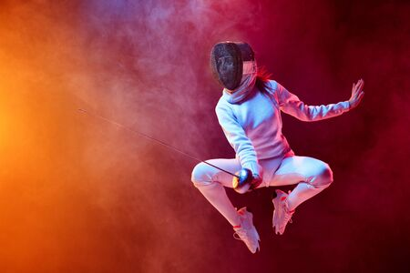 Blooming. Teen girl in fencing costume with sword in hand isolated on black background, neon lighted smoke. Practicing and training in motion, action. Copyspace. Sport, youth, healthy lifestyle.