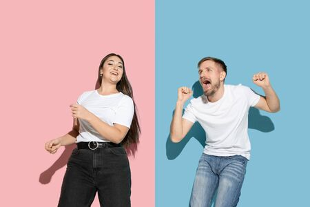 Celebrities. Dancing, moving, having fun. Young, happy man and woman in casual clothes on pink, blue bicolored background. Concept of human emotions, facial expession, relations, ad. Beautiful couple.