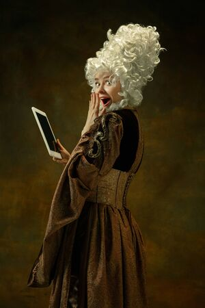 Astonished using tablet. Portrait of medieval young woman in brown vintage clothing on dark background. Female model as a duchess, royal person. Concept of comparison of eras, modern, fashion, beauty.
