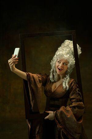 Prendre un selfie. Portrait de jeune femme médiévale en vêtements vintage avec cadre en bois sur fond sombre. Modèle féminin en duchesse, personne royale. Concept de comparaison des époques, de la mode, de la beauté.