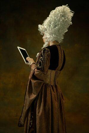 Utiliser une tablette pour être en ligne. Portrait de jeune femme médiévale en vêtements vintage marron sur fond sombre. Modèle féminin en duchesse, personne royale. Concept de comparaison des époques, moderne, mode, beauté. Banque d'images