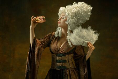Eating burger impressed. Portrait of medieval young woman in brown vintage clothing on dark background. Female model as a duchess, royal person. Concept of comparison of eras, modern, fashion, beauty. Stock fotó